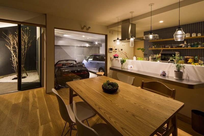 神戸の風景と愛車で挟まれたリビング ほぼ平屋での生活空間 : 西岡本のガレージハウス (ガレージ ダイニングキッチン フロントコート)