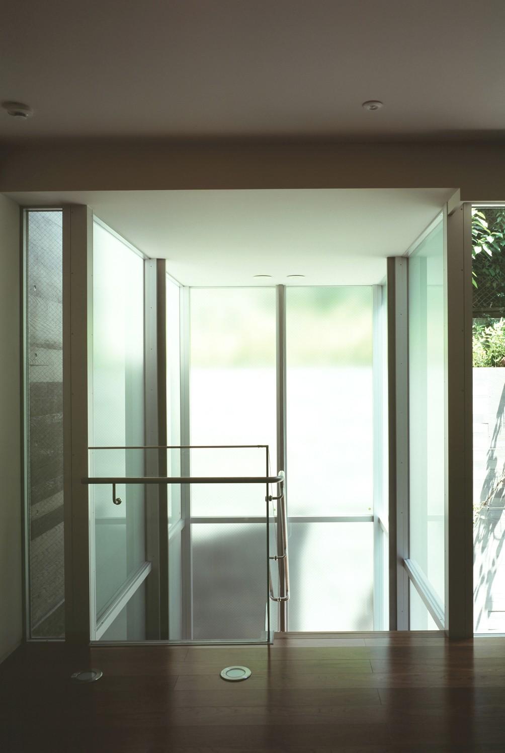 リビングダイニング事例:中庭へ下りて行くガラス張り階段室の様子(HIROO FLAT:地形への応答)