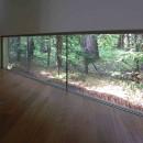 中軽井沢、地窓から裏手の広大な森が目に入る緑に囲まれた住まいの写真 エントランスホール突き当りの地窓からは隣地の広大な原生林が借景として見えるようになっている