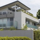 ミッドセンチュリーテイスト 成城にてゆったりと住まうの写真 外観を斜め方向から見る。右奥は世田谷区保存樹木であるクスノキ