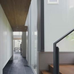 ミッドセンチュリーテイスト 成城にてゆったりと住まう (玄関ホール突き当りの二階への階段まわりの様子)