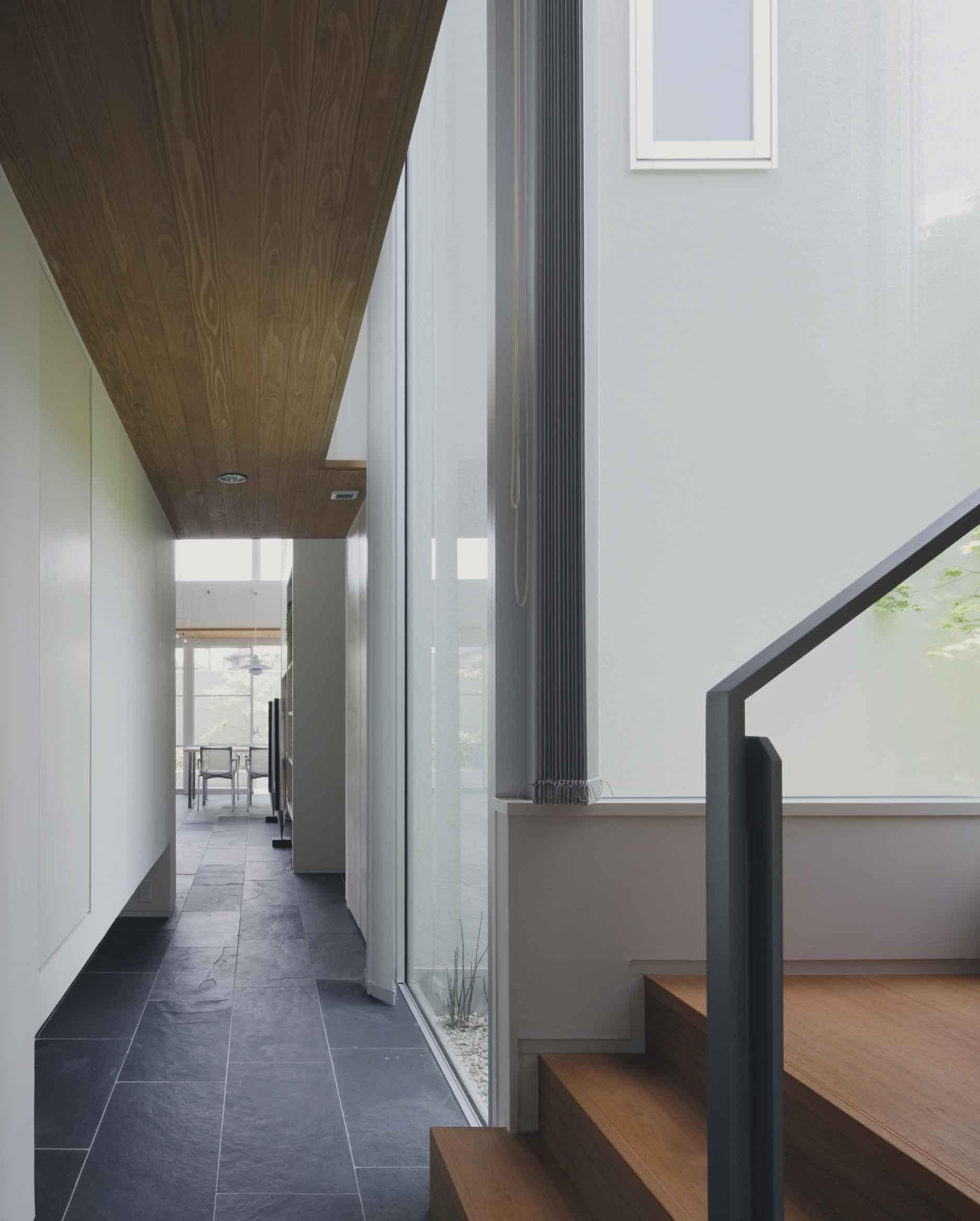 玄関事例:玄関ホール突き当りの二階への階段まわりの様子(ミッドセンチュリーテイスト 成城にてゆったりと住まう)