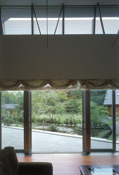 中軽井沢、地窓から裏手の広大な森が目に入る緑に囲まれた住まい (リビング)