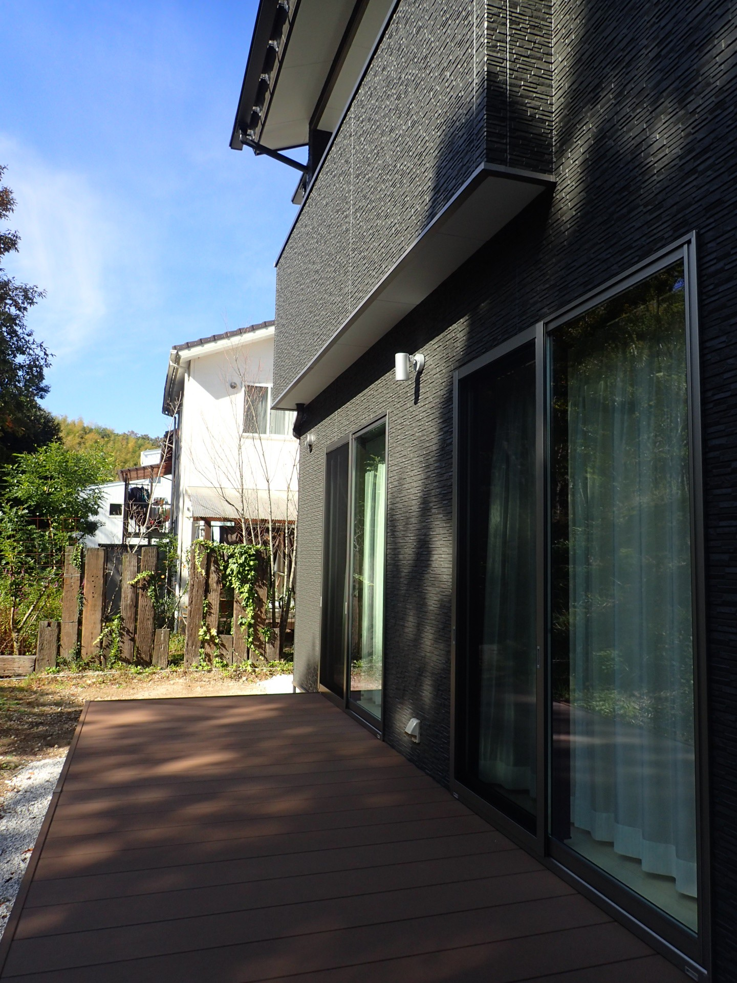外観事例:ウッドデッキ(白と黒を基調としたシンプルモダンな家)