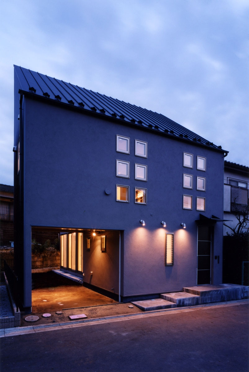 (西東京市)ひばりが丘の木造3階建ての家の写真 外観夕景、ガレージが庭へとつながっています