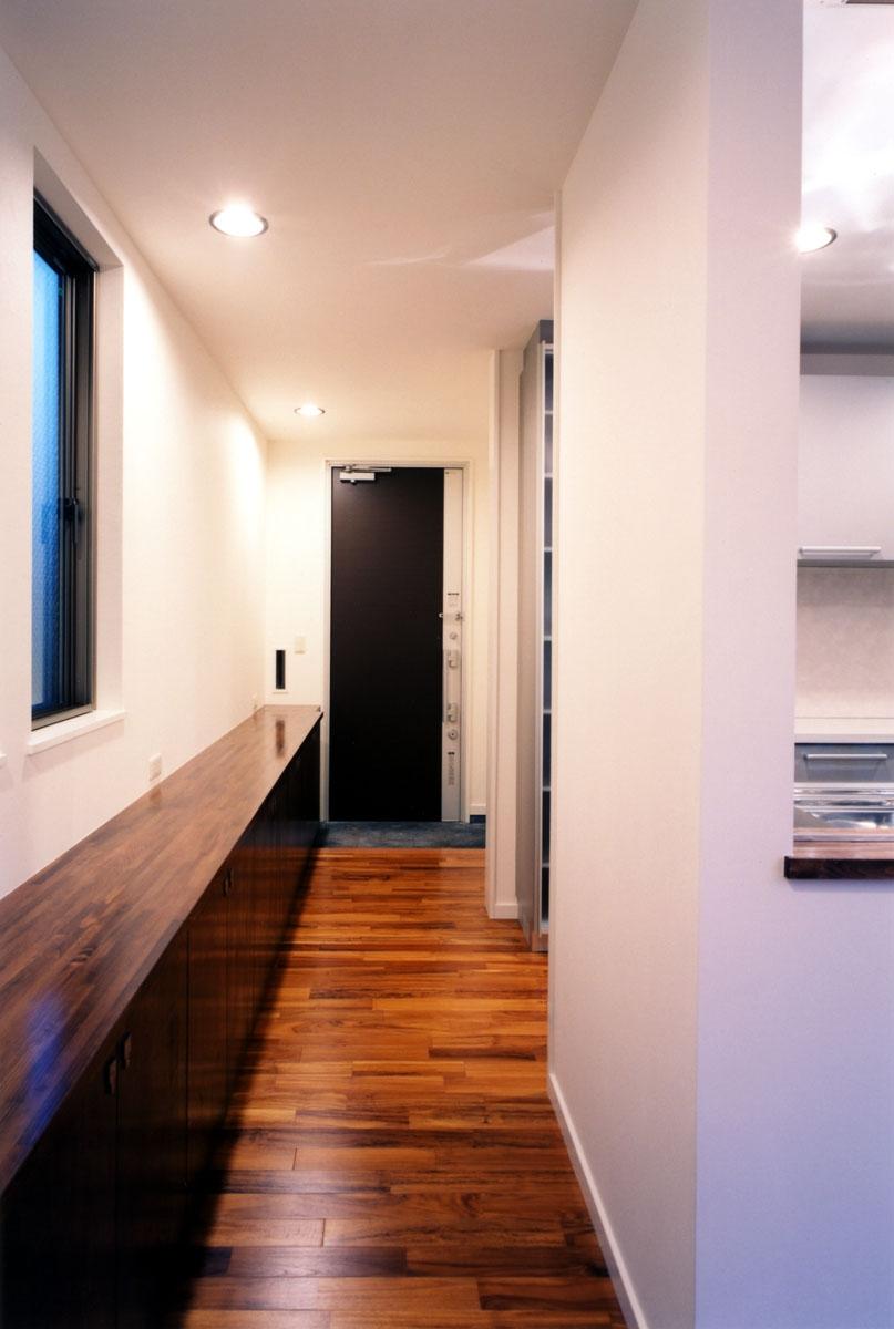 (西東京市)ひばりが丘の木造3階建ての家の写真 1階の玄関およびホール長い収納棚を設けています