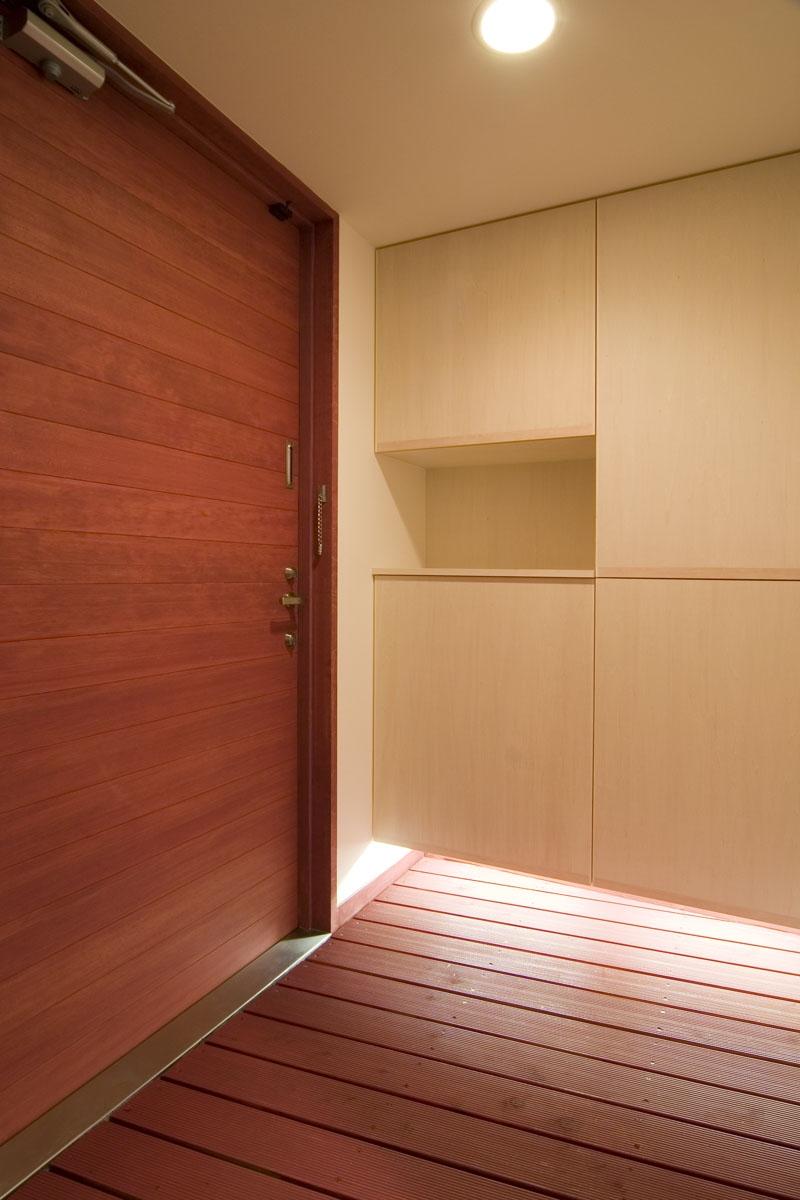 地平線の見える崖地の家の部屋 シナ合板でつくった下足入れのある玄関