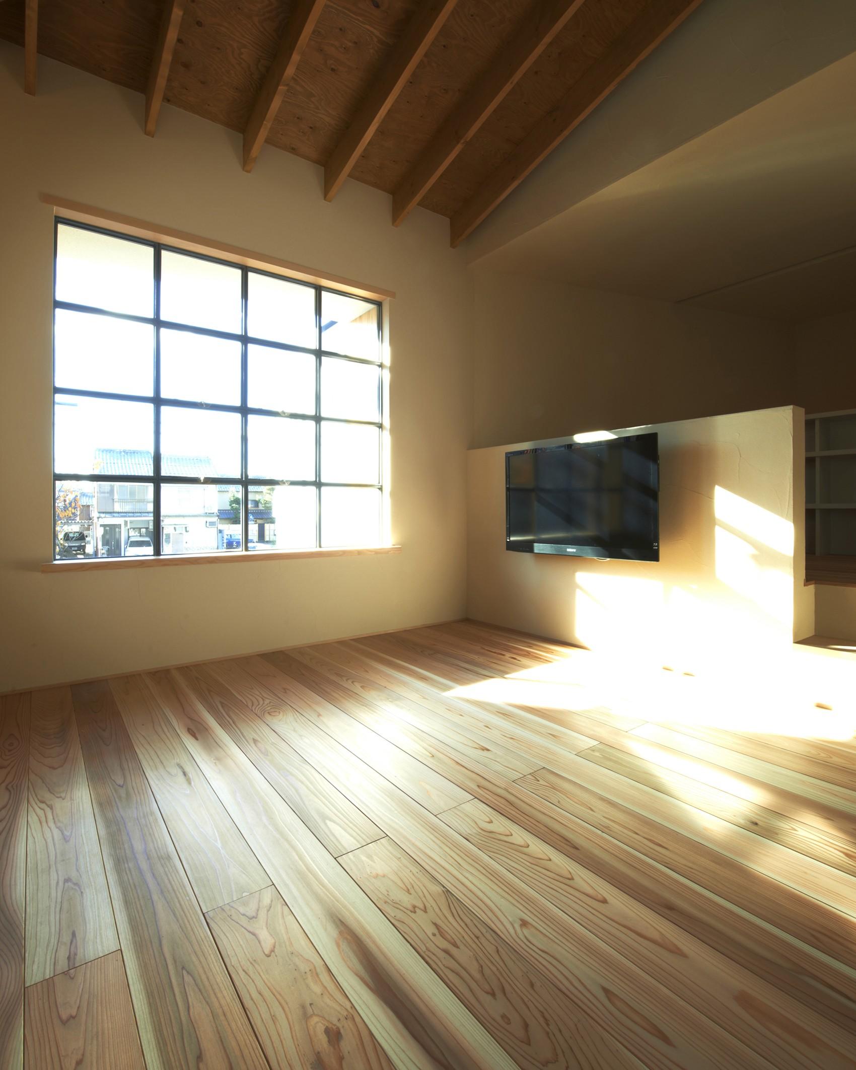 リビングダイニング事例:居間スペースよりスチールサッシを通して外を見る。(木造町の離れ)