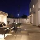 モダン・リゾートスタイルの白いコートハウスの写真 テラス(夜景)