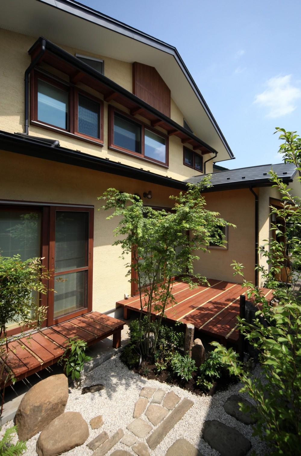 家事が楽な和みの木の家 (ウッドデッキと草木の庭のある外観)