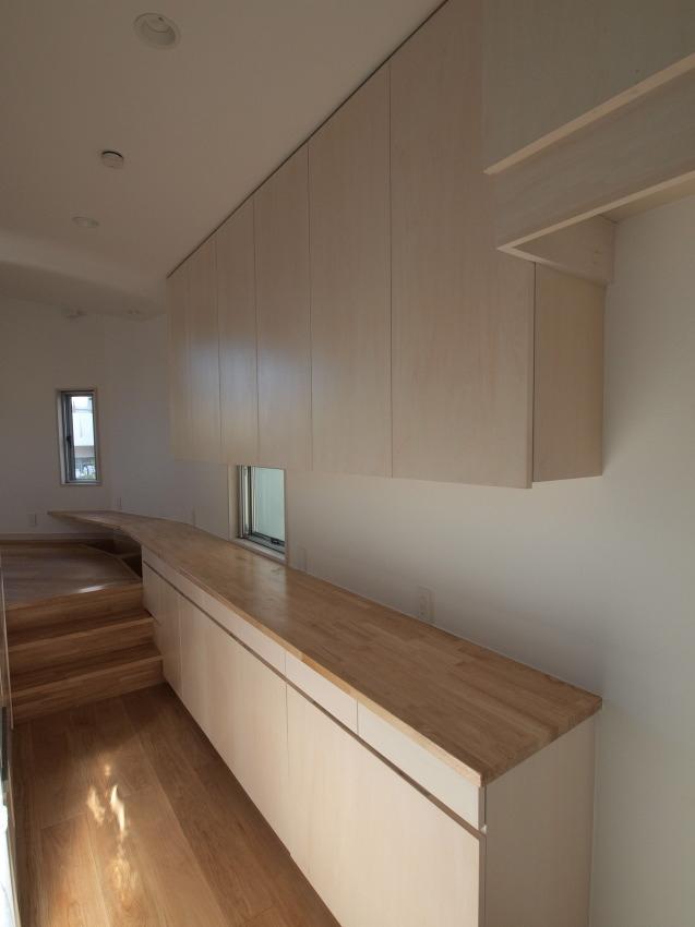 変形旗竿地に建つ半地下スキップフロアの家の写真 キッチン背面の収納棚