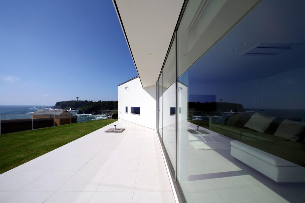 海と庭を楽しめるプライベートなタイルテラス (浅薄の家(せんぱくのいえ)~海を眺める白い家~)