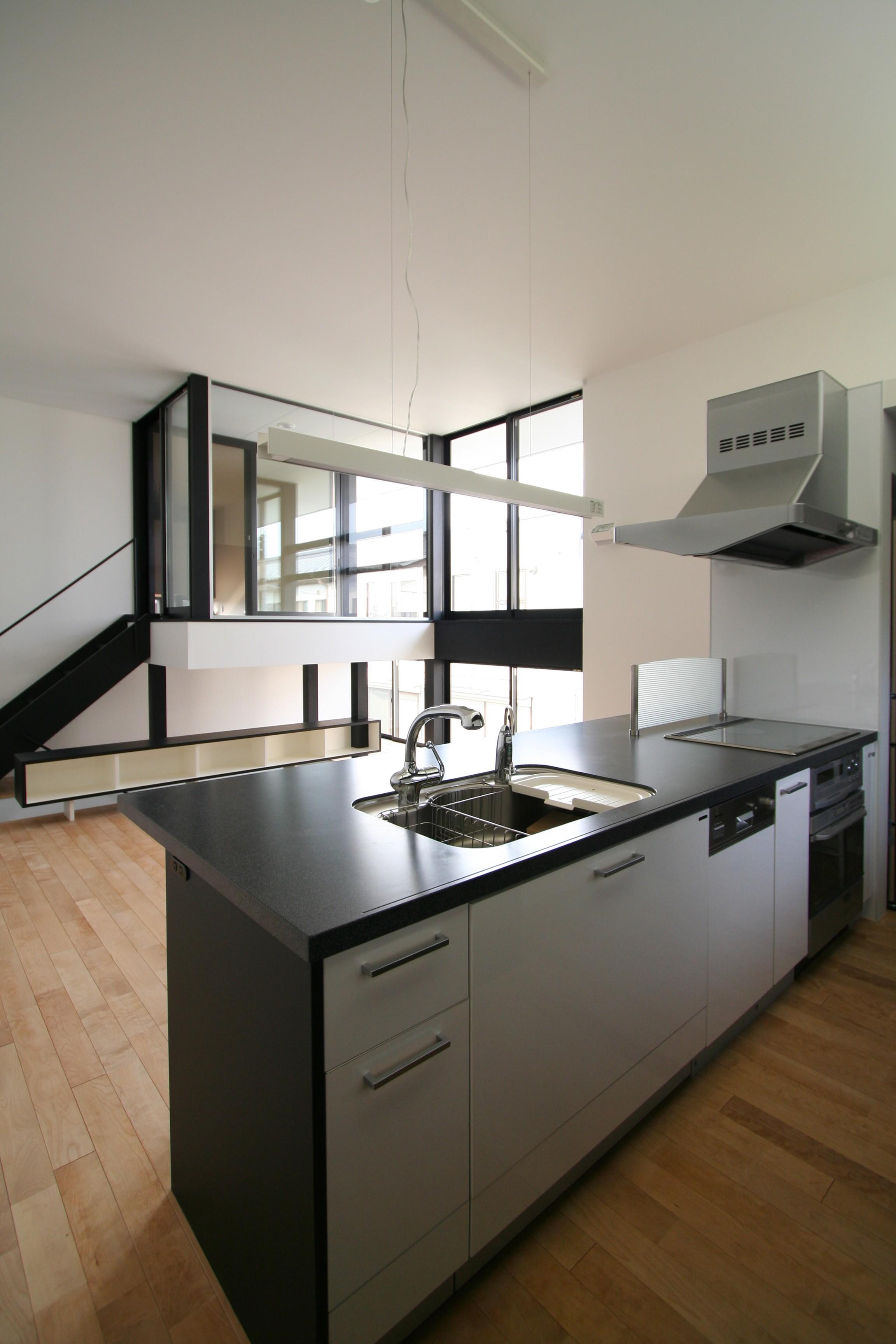 リビングダイニング事例:キッチンからリビングを見る(ミニマルデザインのハコ型の家)