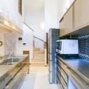 家族が集まる広々としたLDKを中心に、居心地と家事効率を両立させた住まい。の写真 キッチンの天井は吹き抜けに。