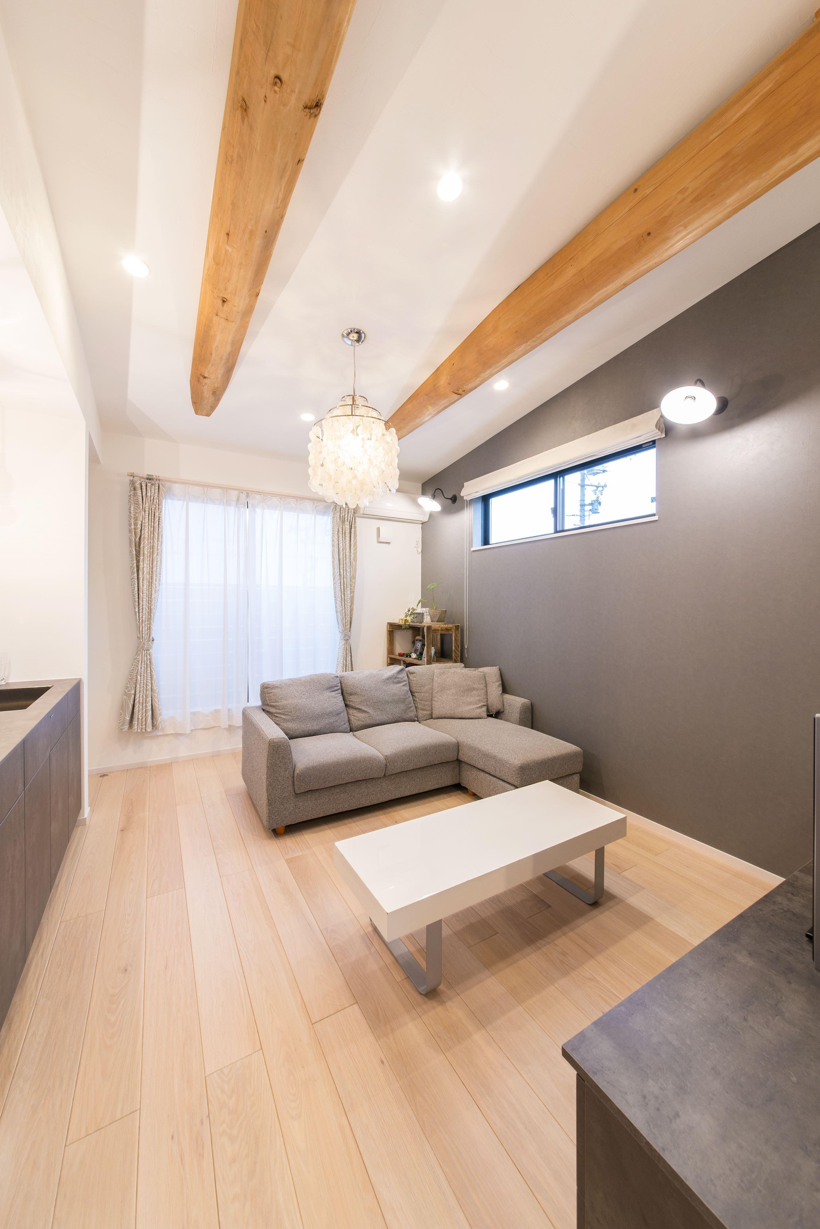 リビングダイニング事例:現地調査の際に見つけた2本の松の梁を現わしにするために勾配天井に。(2階を増築して、デザイン性の高い上下分離型の二世帯住宅にリフォーム。)