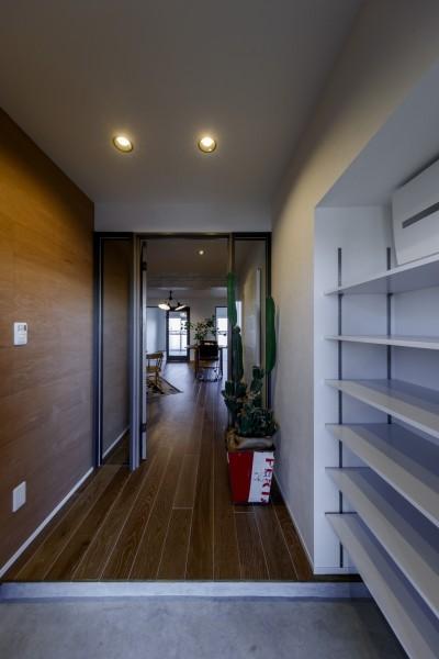 大容量のシューズラックのある玄関 (ファッションを楽しむご夫婦のための家)