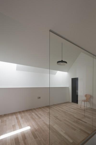 階段区画ガラスごしにみるリビング (さいたまの旗竿敷地の家 OUCHI-21)
