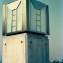 オープンテラスがある週末邸宅:コンクリート構造の住宅設計の写真 外灯