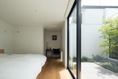 中庭に面した開放的な主寝室 (茅ヶ崎の家〜旗竿敷地に建つ三つの庭を持つ家)