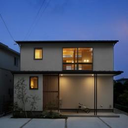 神社の緑を借景としたスキップフロアの家 (外観夕景)