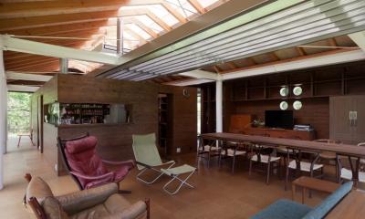 都幾川縁りのハイブリッド・ハウス/Onさんの家 (開放的で屋根構造が見えるリビング・ダイニング。家具はミッドセンチュリー)