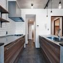 壁・天井もキッチンカウンターもモルタル仕上げの無骨でラフなマンションリノベーションの写真 サニタリーとつながるキッチン