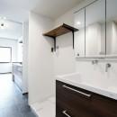 壁・天井もキッチンカウンターもモルタル仕上げの無骨でラフなマンションリノベーションの写真 キッチンとつながるサニタリー