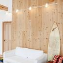 目の前の海風がよく入り、海を感じてのんびりとくつろげる家の写真 ダクトレールの照明が木材の壁に映える