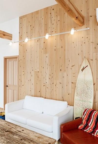目の前の海風がよく入り、海を感じてのんびりとくつろげる家 (ダクトレールの照明が木材の壁に映える)