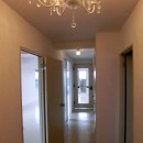 ビビットなカラーのキッチンが中心のマンションリフォームの写真 シャンデリアと廊下も白で明るい空間に