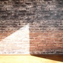 レンガ調のアクセントクロスと収納力抜群の壁面可動棚のLDK部分リノベーションの写真 リビングダイニング