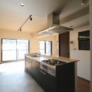 レンガ調のアクセントクロスと収納力抜群の壁面可動棚のLDK部分リノベーションの写真 キッチン
