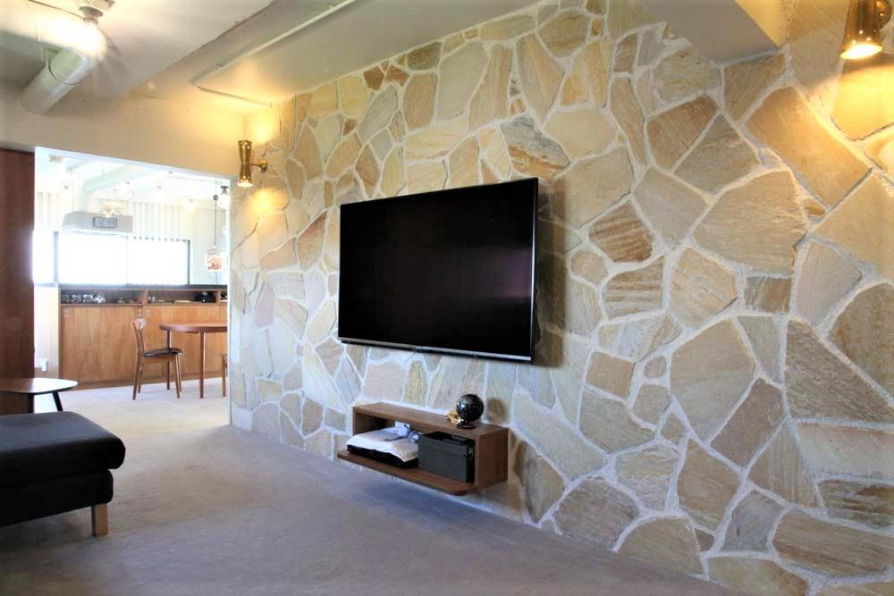 シンプルに暮らせる。ヴィンテージスタイルの家 (石張りの壁が印象的なリビングスペース)