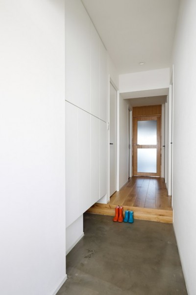 """採光が届きにくい玄関側は白を基調に (南向きの暖かなリビングに、子供たちの成長を見守る""""大黒柱""""のあるマンション。)"""
