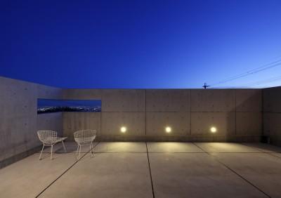 南の隣家を気にせず南東に広がる夜景を見下ろすバルコニー (高台の家 –コンクリート打ち放し –)