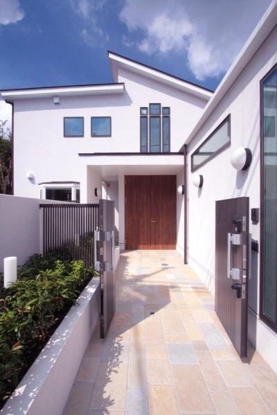 石畳の玄関アプローチ (善福寺の家(広い庭とビルトインガレージのある2世帯住宅))