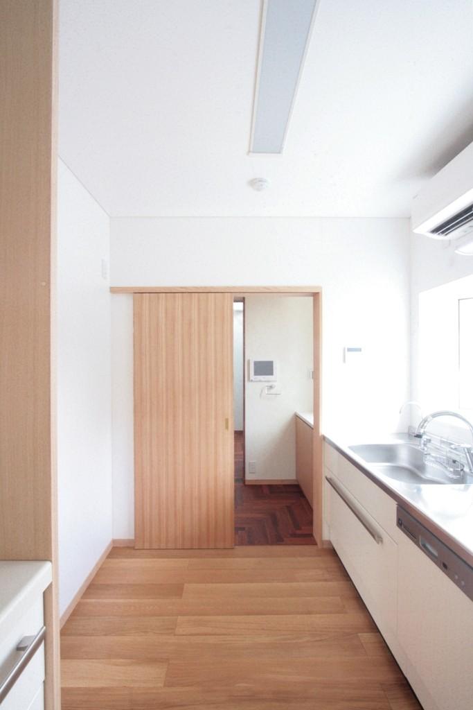 善福寺の家(広い庭とビルトインガレージのある2世帯住宅) (南東の角に設けた明るいキッチン(玄関と勝手口に隣接))