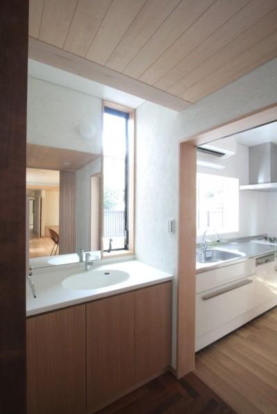 玄関脇の洗面コーナーとキッチン (善福寺の家(広い庭とビルトインガレージのある2世帯住宅))