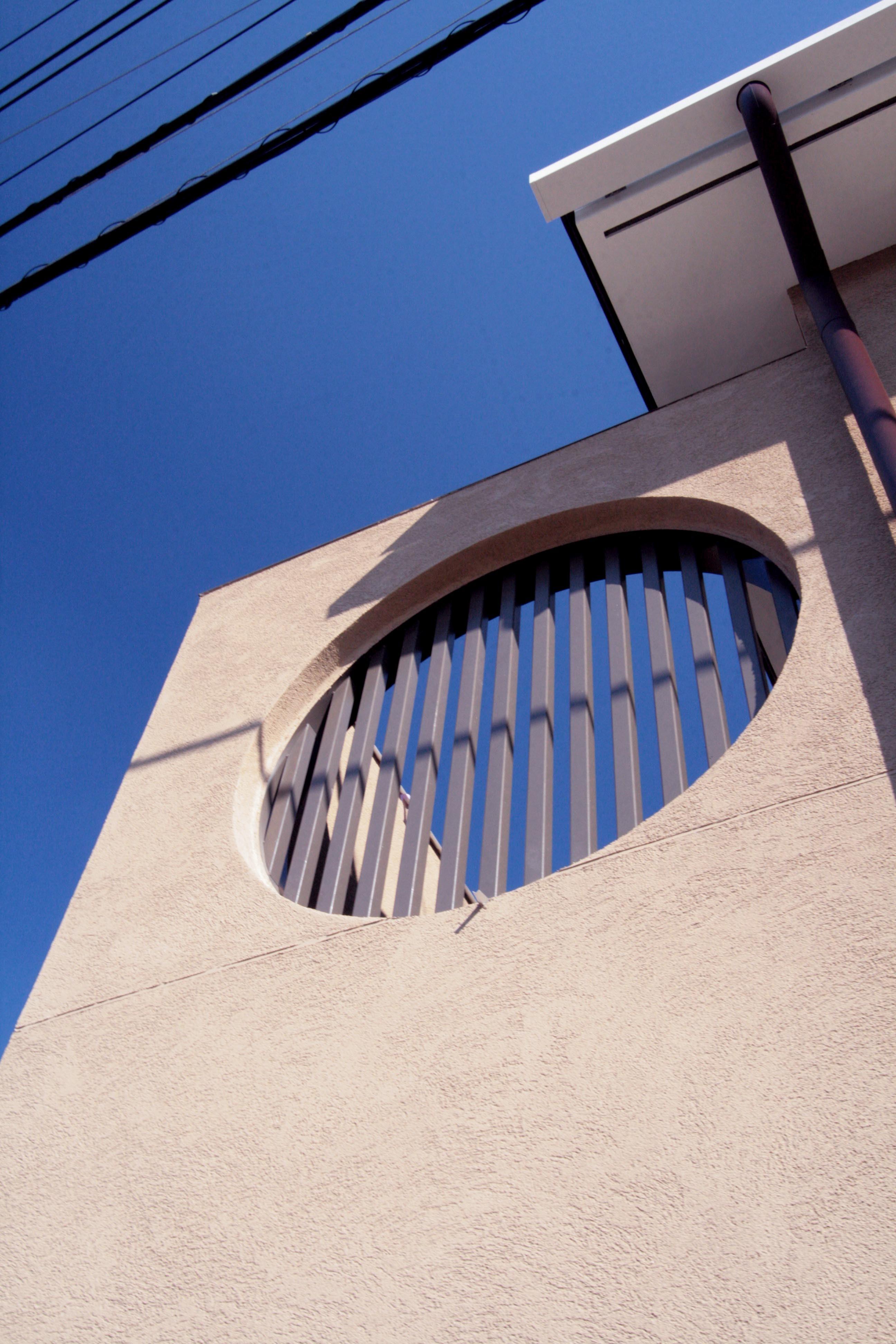 外観事例:外観(左官による外壁と格子付の円形開口)(大泉学園の家(薪ストーブを設けた吹抜けを中心とした自然素材の家))