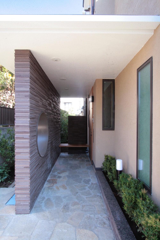 大泉学園の家(薪ストーブを設けた吹抜けを中心とした自然素材の家) (目隠し壁とベンチを設けた玄関アプローチ)