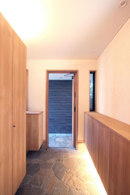 大泉学園の家(薪ストーブを設けた吹抜けを中心とした自然素材の家) (玄関ホール(間接照明と木製扉の玄関))
