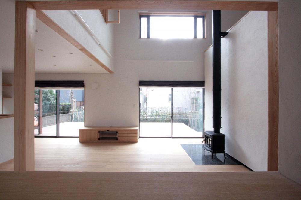 大泉学園の家(薪ストーブを設けた吹抜けを中心とした自然素材の家) (リビング(吹き抜けと薪ストーブのリビング、南庭のウッドデッキを望む))