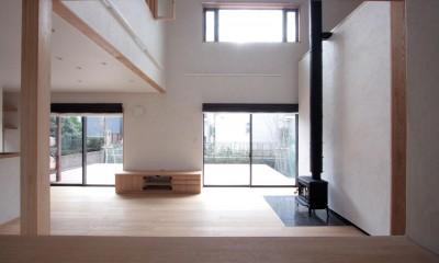 リビング(吹き抜けと薪ストーブのリビング、南庭のウッドデッキを望む)|大泉学園の家(薪ストーブを設けた吹抜けを中心とした自然素材の家)