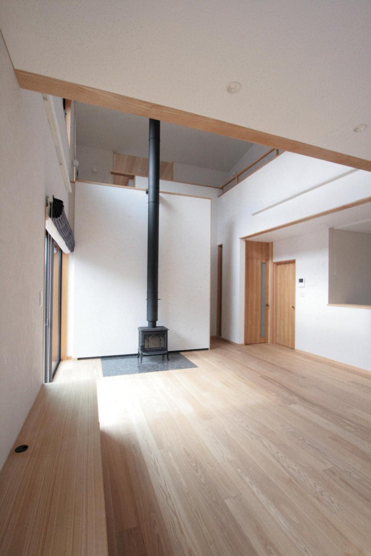 大泉学園の家(薪ストーブを設けた吹抜けを中心とした自然素材の家) (リビング・ダイニング(ダイニングよりリビングを望む))
