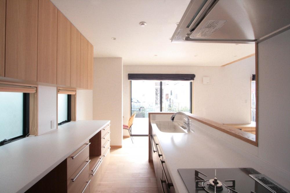 大泉学園の家(薪ストーブを設けた吹抜けを中心とした自然素材の家) (キッチン(食品庫より望む))