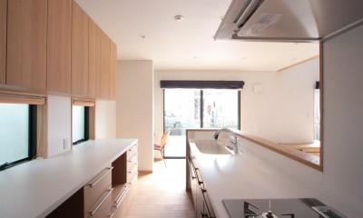 キッチン(食品庫より望む)|大泉学園の家(薪ストーブを設けた吹抜けを中心とした自然素材の家)