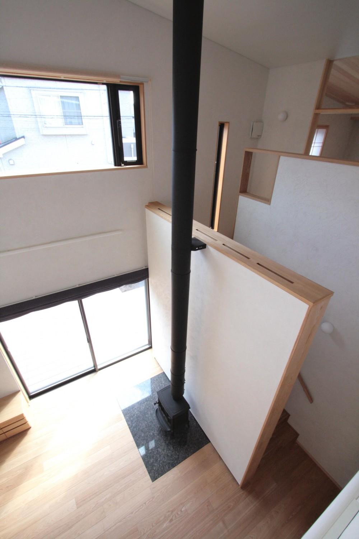 大泉学園の家(薪ストーブを設けた吹抜けを中心とした自然素材の家) (吹き抜け(下階のリビング、薪ストーブ、階段廻りを望む))