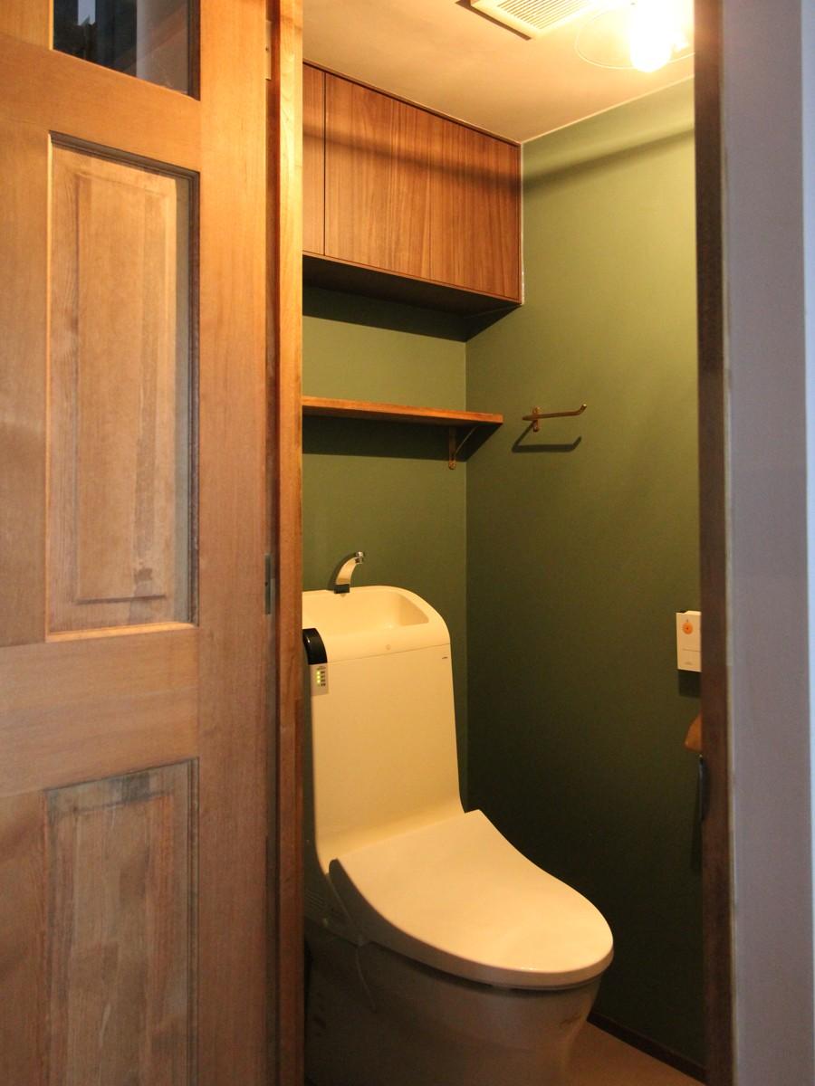 """好き""""に囲まれて暮らすアトリエのあるリノベーション (落ち着いたグリーンのクロスのトイレ空間)"""