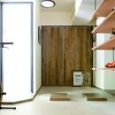 アイアンフレームのオリジナルキッチンと飛び床の土間の家の写真 玄関土間
