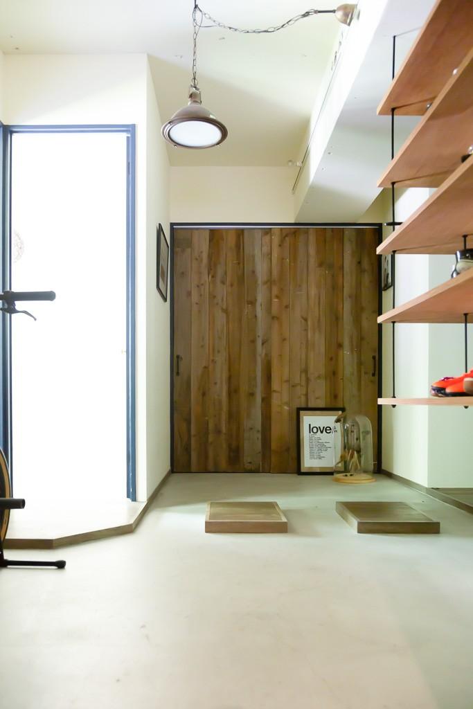 アイアンフレームのオリジナルキッチンと飛び床の土間の家 (玄関土間)